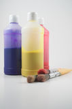 Painting supplies. Three bottles of paint and three paint brushes Royalty Free Stock Image