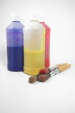Painting supplies. Three bottles of paint and three paint brushes Royalty Free Stock Photography