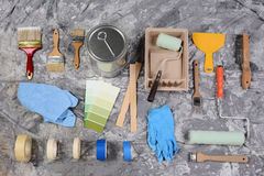 Painting Supplies. High angle shot of the tools needed to paint spread out on a drop cloth. Items include, paint can, brushes, rollers, tray, tape, color chart Royalty Free Stock Image
