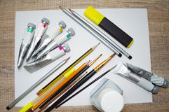 Painting supplies on white blank sheet of paper. Tubes of paint, paint brushes, pencils and marker on white blank sheet of paper on wooden table Royalty Free Stock Photography
