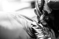 Painting a tattoo. Hands of the artist painting a tattoo on men's skin. Close up. Horizontal image. Black and white stock photo