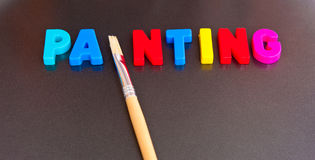 Painting. Text ' painting ' in colorful uppercase letters with letter ' i ' replaced by a clean brush on a dark background Royalty Free Stock Image