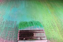 Painting textured background shades of green and blue. Paintbrush centered with fresh paint on bristles. Bright artsy background royalty free stock image