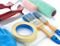 Painting tools on white background. Paint rollers, brushes, drop cloth, masking tape and gloves royalty free stock photography