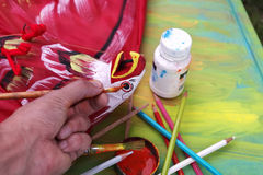 Painting A Toy Bird. Artist hand painting a paper made bird, concept of creativity stock photography
