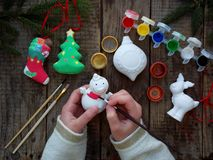 Painting toys for Christmas decorations from porcelain with your own hands. Children DIY concept. Making xmas tree decoration. Stock Image