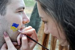 Painting ukrainian flag  on the male's face Stock Images