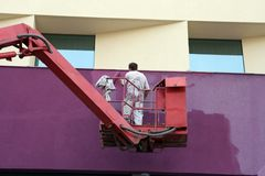 Painting wall. Worker paint wall of modern building Royalty Free Stock Images