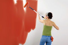Painting the wall. Woman painting on wall using paint roller Stock Photography