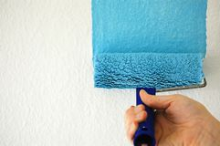 Painting a wall with blue paint stock images