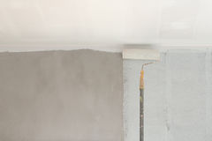 Painting a wall and ceiling with roller Stock Images