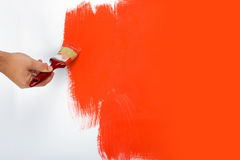 Painting a wall red. Painting a white wall red with a small paintbrush Royalty Free Stock Photos