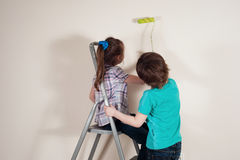 Painting the wall together. Boy and girl  with paddle rollers making renovation in the house Royalty Free Stock Image