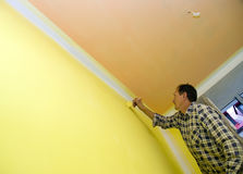 Painting a wall in yellow. A contractor painting a wall in yellow using a brush Royalty Free Stock Photos