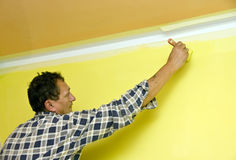 Painting a wall in yellow. A contractor painting a wall in yellow using a brush Stock Image