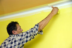 Painting a wall in yellow. A contractor painting a wall in yellow using a brush Stock Photo
