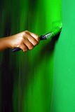 Painting walls. Painting a wall with paint brush in green Stock Photos