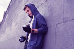 Good-looking dangerous guy in blue hoodie leaning on the wall stock photos