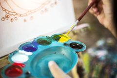Painting water color with brush and palette. Close up shot painting water color with brush and palette in dark light. art creation concept royalty free stock photos