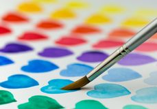 Painting watercolor hearts with a paintbrush. Shallow depth of f Royalty Free Stock Photos