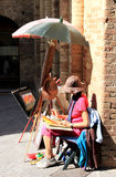 Painting woman in San Gimignano, Italy. Walking through the Old City of the Italian town of San Gimignano,  UNESCO has declared it a World Heritage Site, means Stock Image