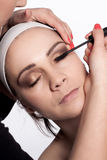 Painting of women eyelashes using mascara. Beauticians paints using mascara eyelashes young brunette women with headband on her head Royalty Free Stock Images