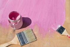 Painting wood background in blue color tassels. The painting process of the wooden background in pink color. Two brushes with the paint in a glass jar. A Royalty Free Stock Images