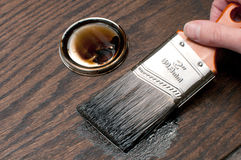 Painting wood in brown with brush Royalty Free Stock Images