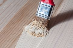 Painting wood with a brush. Painting on a wood surface with a brush Stock Image