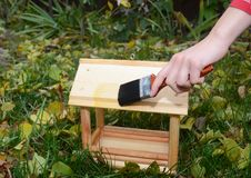 Painting wooden bird feeder for rain protection. Repair bird feeder covering with drying oil. - Image. Painting wooden bird feeder for rain protection. Repair stock photography