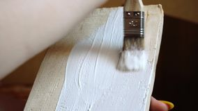 Painting a wooden board with a white paint brush close-up