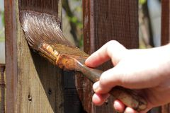 Painting the wooden garden fence. New paint for the wooden garden fence Royalty Free Stock Photography