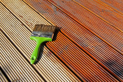 Painting wooden patio deck with protective oil Royalty Free Stock Image