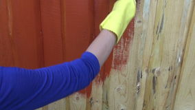 Painting wooden plank house wall with paintbrush stock footage