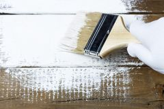 Painting a wooden surface with white paint, a gloved hand holding a paint brush stock photography