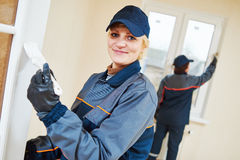 Painting works. Female smiling  painter with paint brush at renovation Royalty Free Stock Photo
