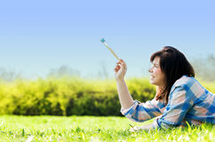Painting the world. Smiling girl on grass with a paintbrush Stock Photos