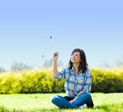 Painting the world. Smiling girl on grass with a paintbrush Royalty Free Stock Photo