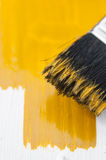Painting. Yellow paint on a brush stock images