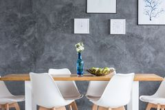 Paintings on grey textured wall. Apples in decorative bowl on wooden table in dining room with paintings on grey textured wall Stock Photo