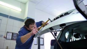 Paintless bucklareparation En man i en blå sweater reparerar stammen på en bilreparation shoppar Reparation av bucklor utan målni stock video