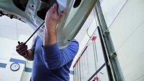 Paintless bucklareparation Förlagen arrangera i rak linje bucklorna på huven av bilen i den automatiska reparationen shoppar, den stock video