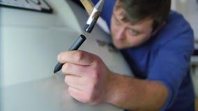 Paintless bucklareparation N?rbildf?rlagen, som reparerar huven av enf?rgad automatisk i en bilreparation, shoppar isolerat i a arkivfilmer