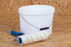 Paintroller and paint bucket. Paint roller and a bucket of white paint Stock Image