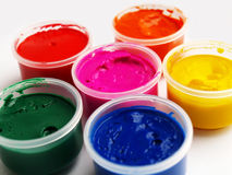 Paints. Open plastic containers of paint in primary colors Stock Photos