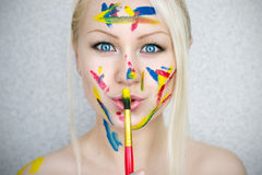 Paints. Blond girl with a brush Royalty Free Stock Photos