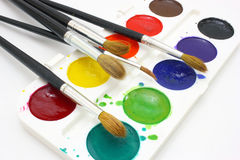 Paints with brushes. Dirty watercolor paints set with brushes after using Stock Images