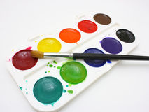 Paints with brushes. Dirty watercolor paints set with brushes after using Stock Photography
