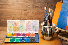 Paints and brushes art supplies in painting studio Royalty Free Stock Photo