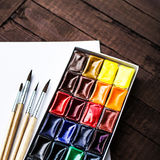 Paints and brushes with blank white paper sheet on vintage woode Royalty Free Stock Images